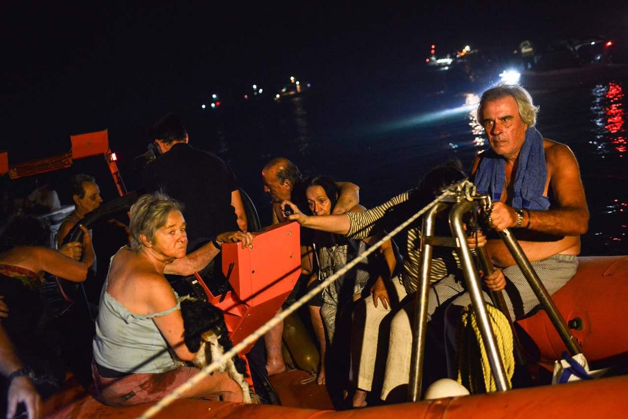 雅典附近的濱海小鎮馬蒂23日遭野火肆虐,救援人員利用船隻撤離民眾。法新社