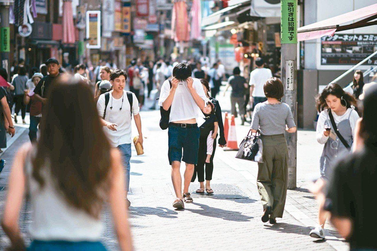由於遭受罕見的嚴重熱浪侵襲,日本政府考慮延長暑假。圖為東京街頭一名男子廿四日用衣...