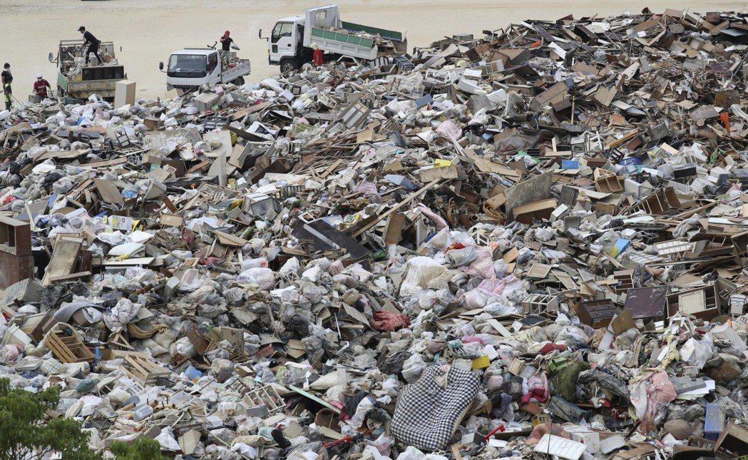 清出來的大批災後垃圾,目前已堆滿各地的臨時垃圾收集場。 圖/美聯社
