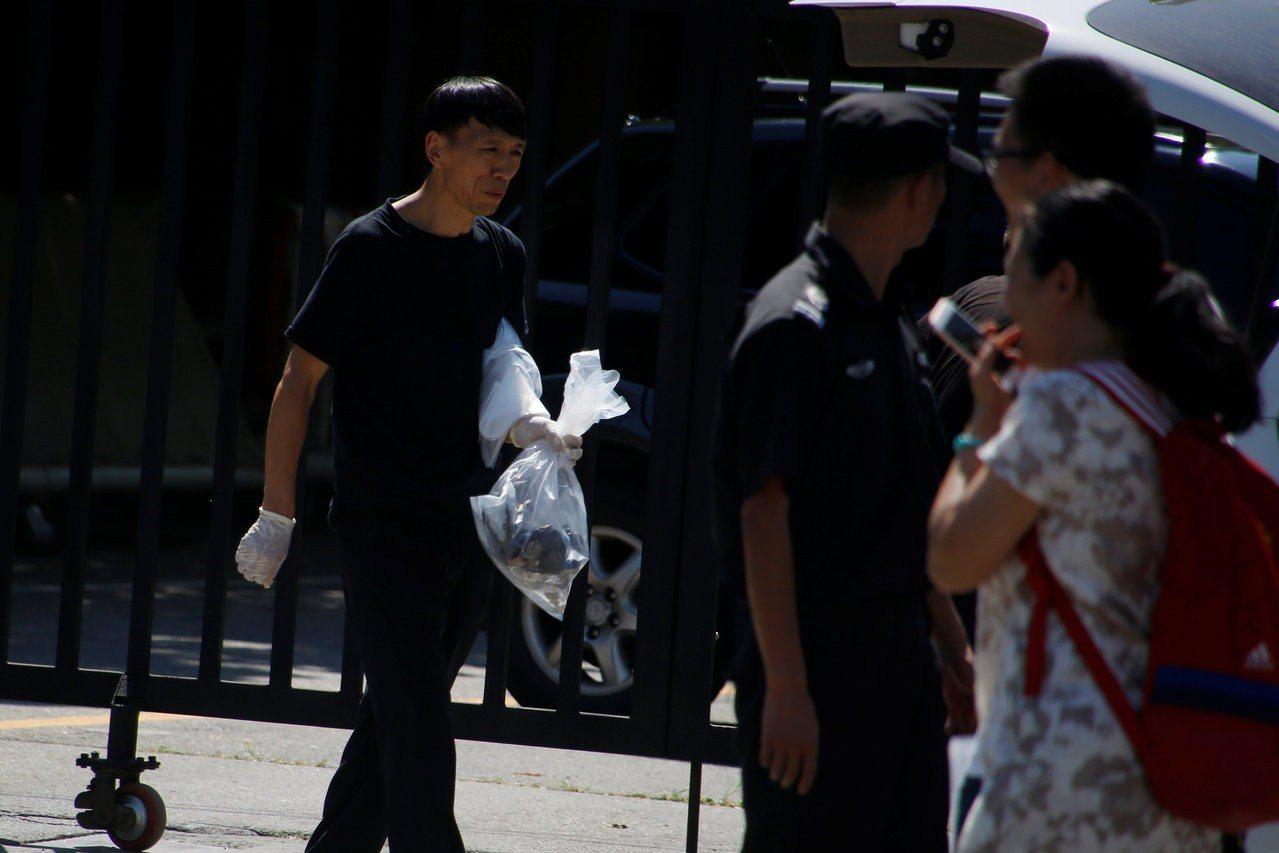 北京美國大使館發生爆炸事件後,現場一名安全人員拿著塑膠袋採集相關證物。路透