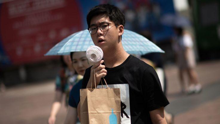 日本遭遇持續性熱浪侵襲,受不了高溫的1名民眾帶著小風扇上街。 (翻攝自網路)