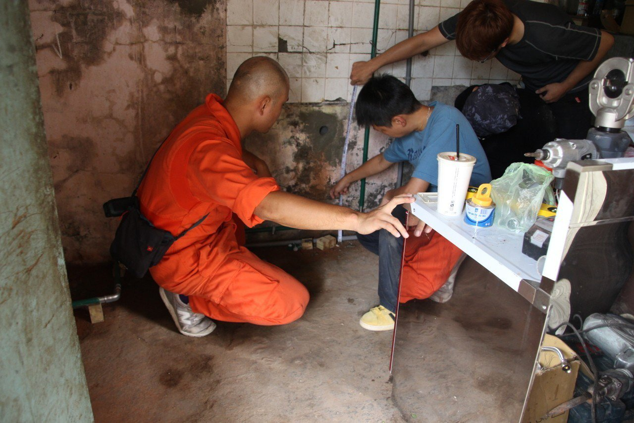 伊甸「羅賴把志工團隊」的水電與木工老師討論廚房修繕方式。圖/伊甸基金會提供