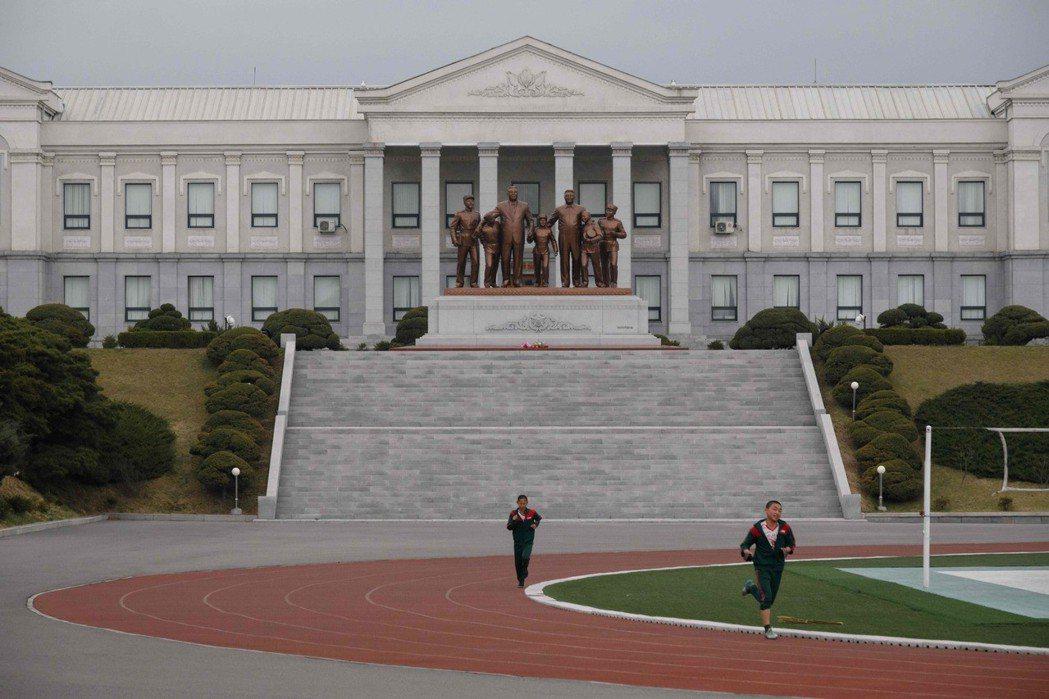 萬景台學院的操場,後方矗立著金日成、金正日父子與男學生並肩而行的銅像。 法新社