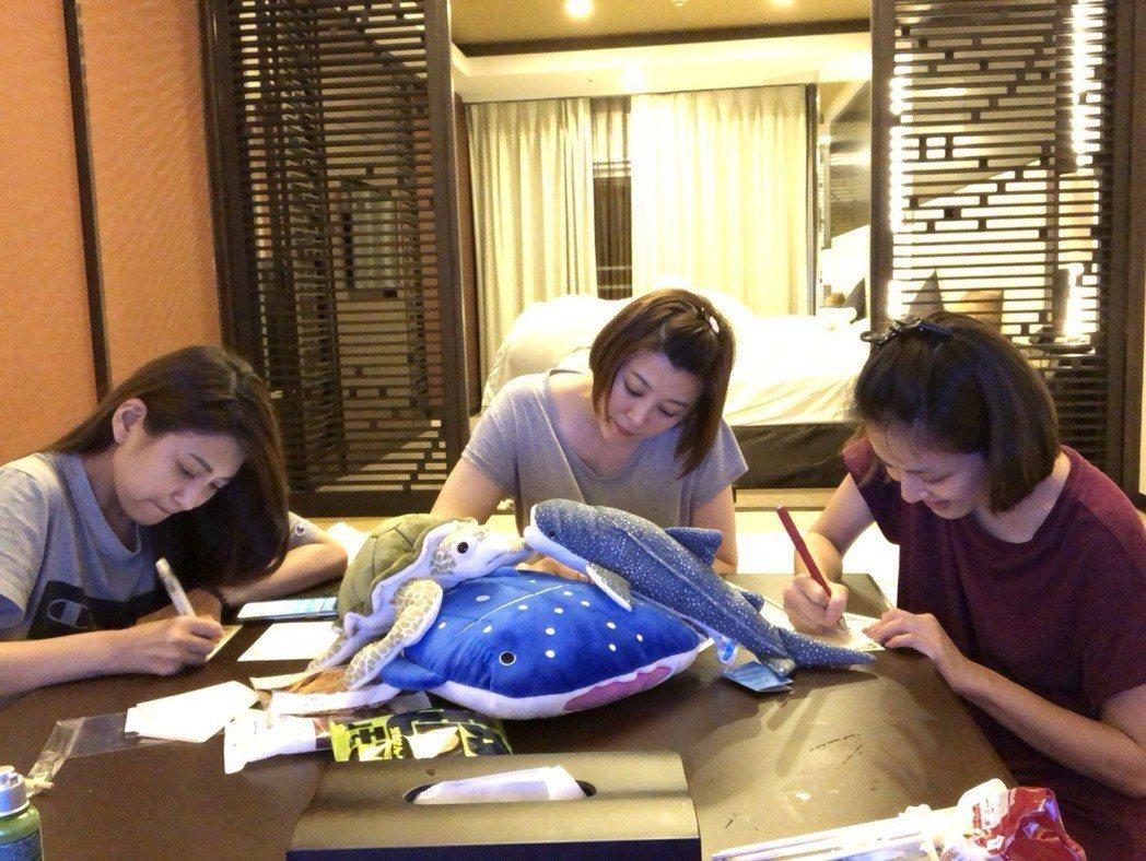 樓心潼(左起)、方馨、蘇晏霈在沖繩寫明信片給自己。圖/方馨提供