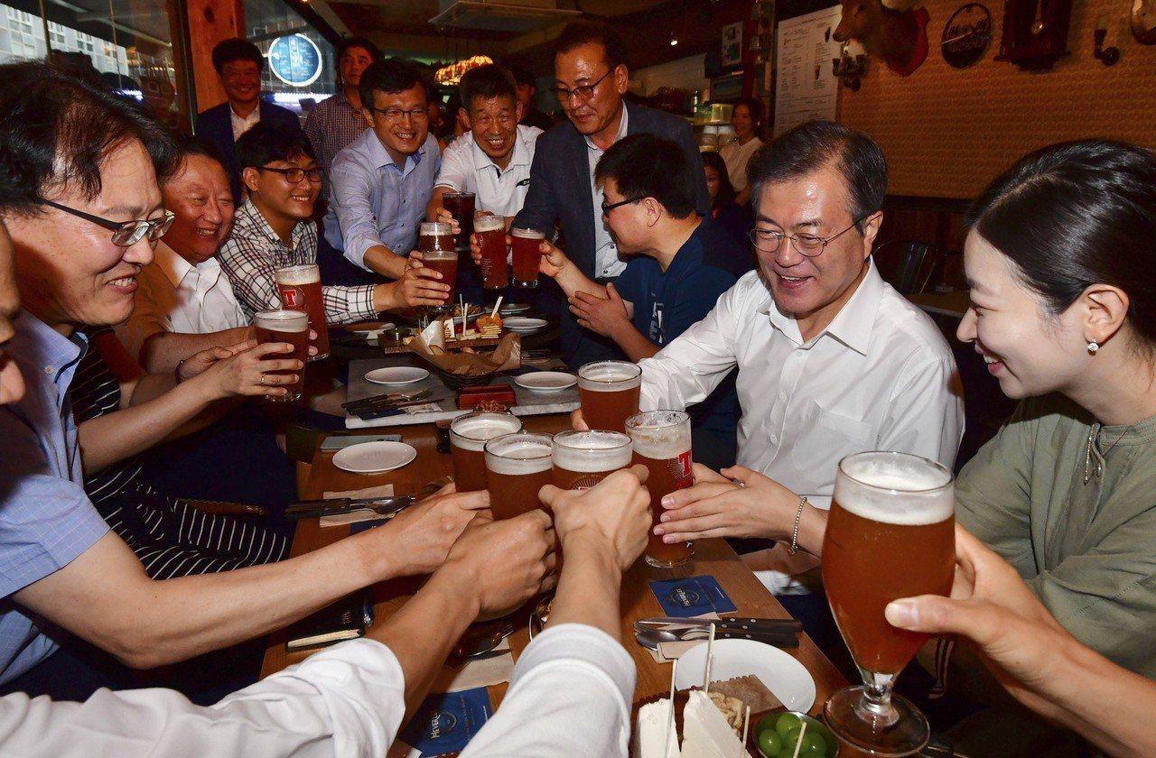文在寅(右二)26日向參與啤酒會議的國民敬酒。歐新社 ※ 提醒您:禁止酒駕 ...