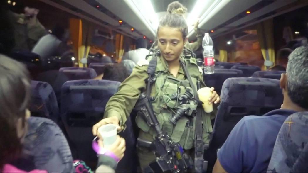 以色列軍(圖中綠色軍裝者)發放飲用水給撤出的白盔隊。 圖/路透社