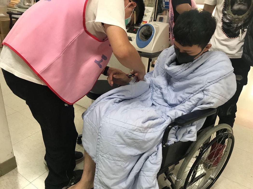 李子森被民眾目擊癱坐在輪椅上看診。圖/讀者提供