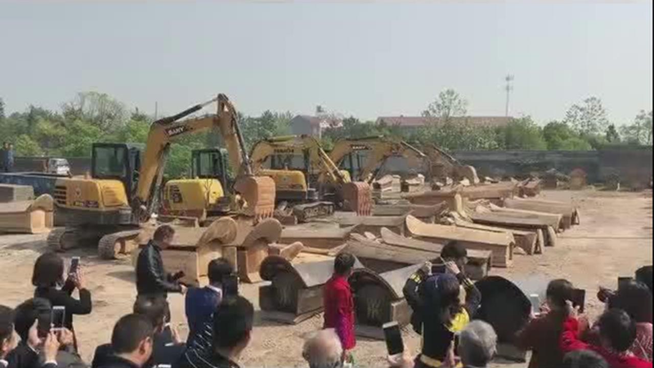 江西某地在推行殯葬改革的過程中,使用機械強行毀壞尚未完工的棺材。(視頻截圖)