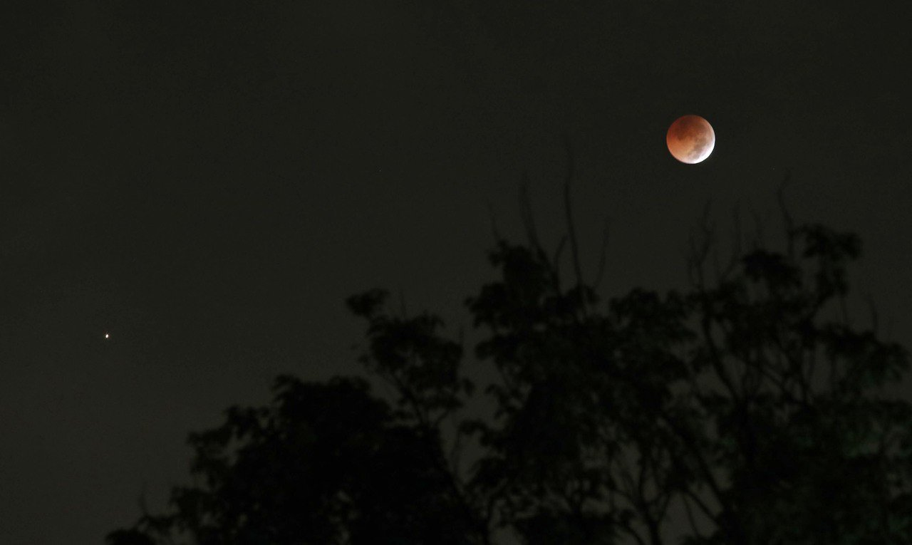 28日凌晨適逢21世紀最長的月全食,「紅火星」與「赤月亮」相距不到10度的景象。...