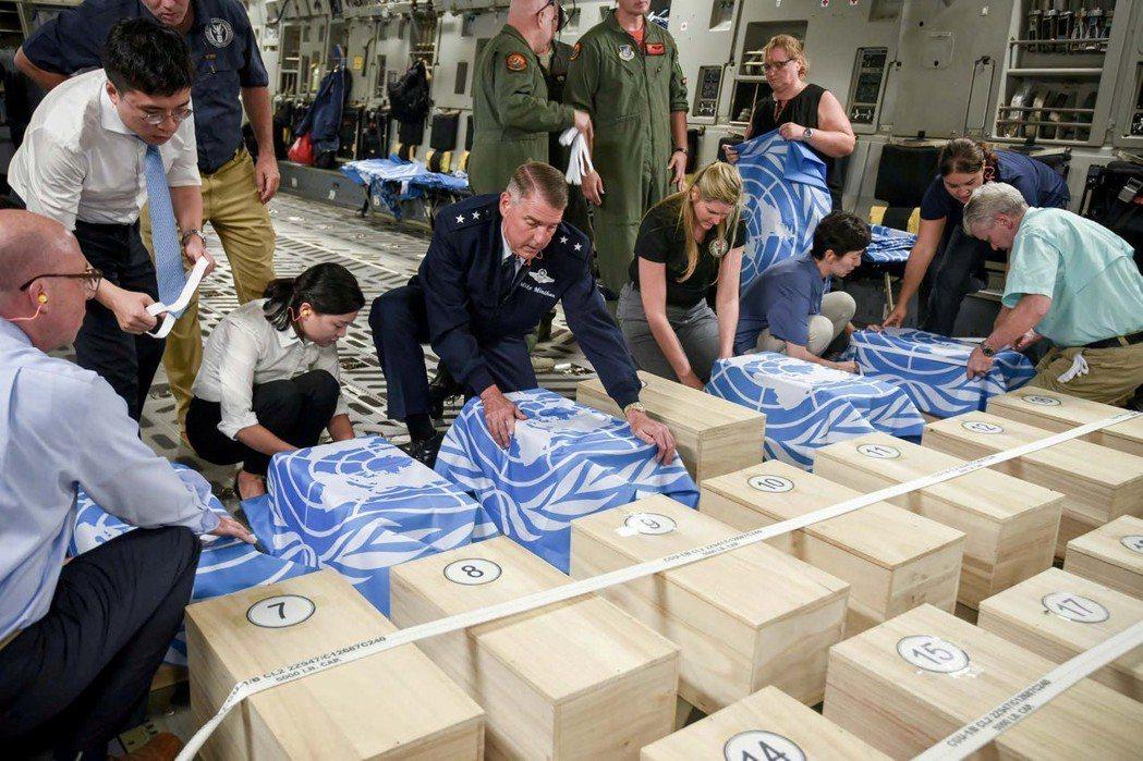 聯合國司令部人員與官員將裝著遺骸的盒子都蓋上聯合國旗。(路透)