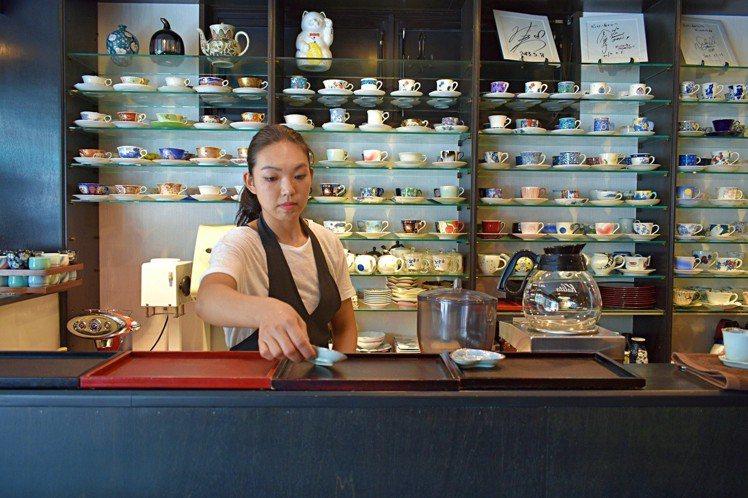 牆面上都是咖啡杯,店員會依據客人選擇的杯子裝杯。圖/記者魏妤庭攝影
