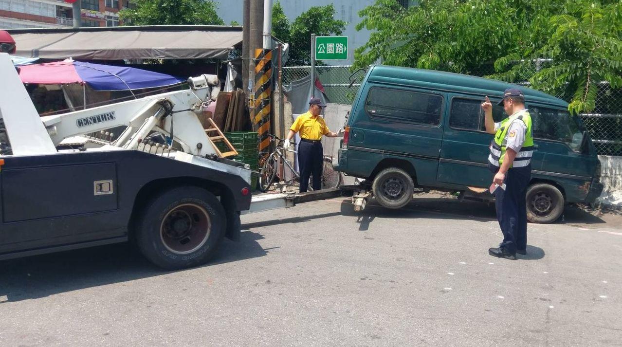 警方在新北市汐止區中正市場拖吊1輛廢棄箱型車,吸引民眾圍觀。圖/新北市汐止警分局...