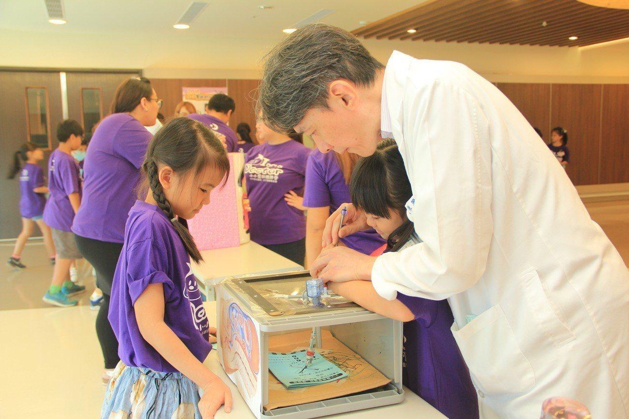 大千醫院小小醫師體驗營上午登場,醫師教小朋友體驗如何使用腹腔鏡開刀。圖/大千醫院...
