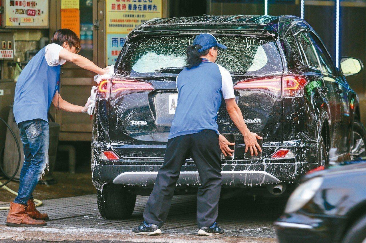 工商界認為,如果時薪調幅高於月薪,對服務業衝擊大。圖為加油站員工賣力洗車。 記者...