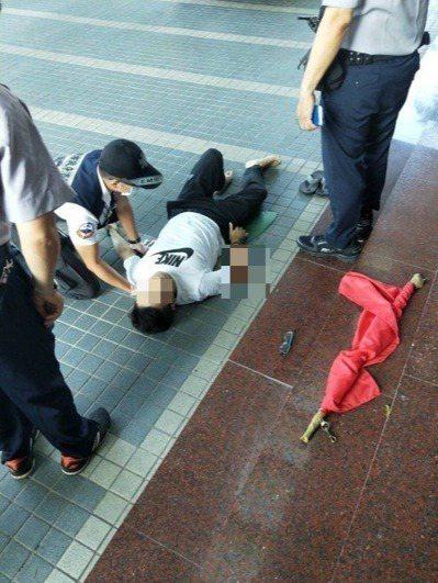 曾姓法警(中)上周四早晨升旗跌落地面。圖/本報資料照