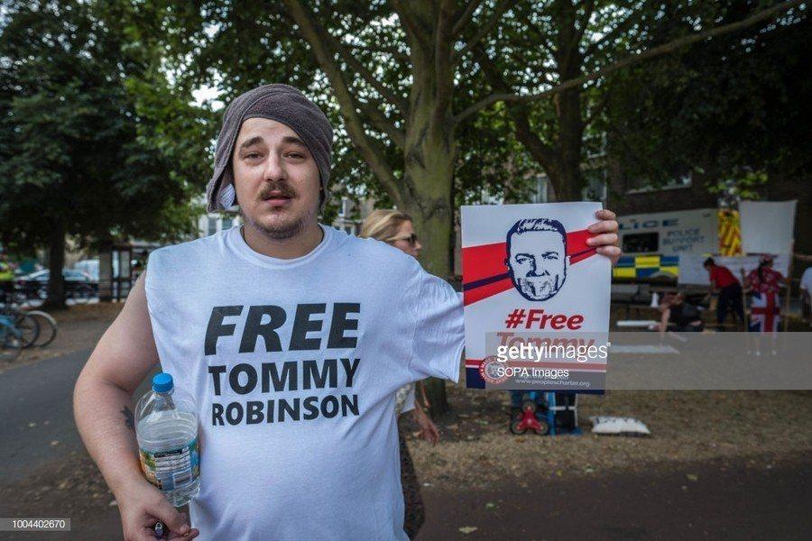 湯米.羅賓森的支持者手持「釋放湯米.羅賓森」立牌,主張英國法庭的判決是對言論自由...