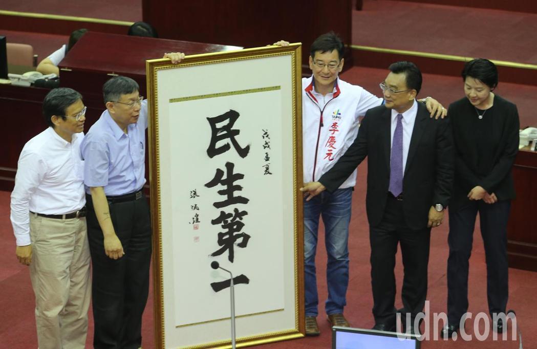 今年五月,議員李慶元(中)贈送「民生第一」的書法匾額,要市長柯文哲(左二)專心在...