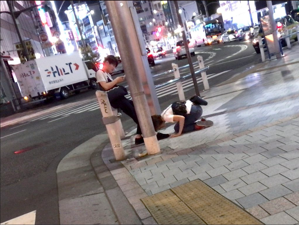 在東京街頭,有名女子對男子行土下座大禮,詢得男子的原諒。圖擷自Twitter