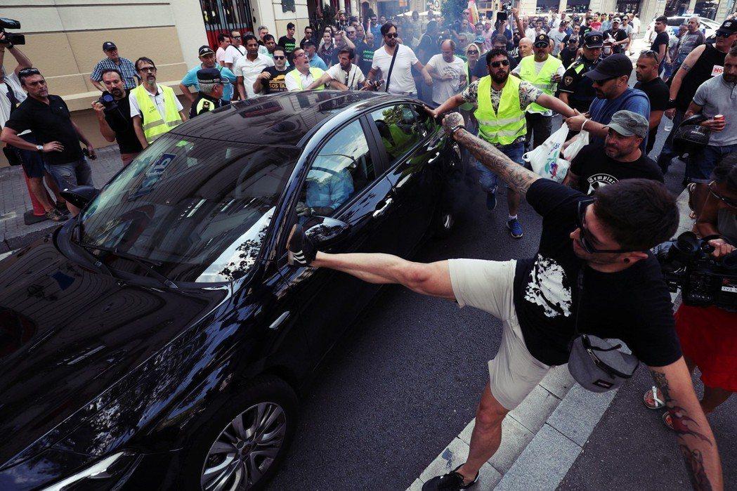 一名罷工的計程車司機,憤怒地飛踢一輛路過罷工區的Uber。自從2014年12月因...