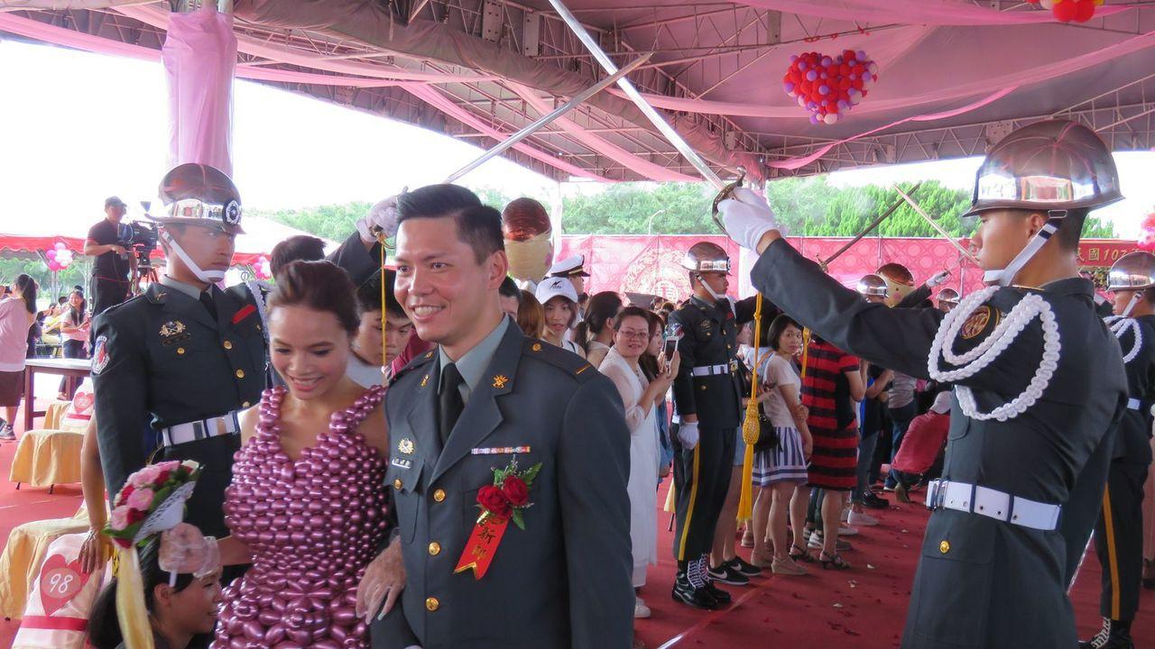 陸軍司令部今天在桃園龍潭大漢營區,舉行107年度聯合婚禮,新人步入陸軍儀隊搭起象...