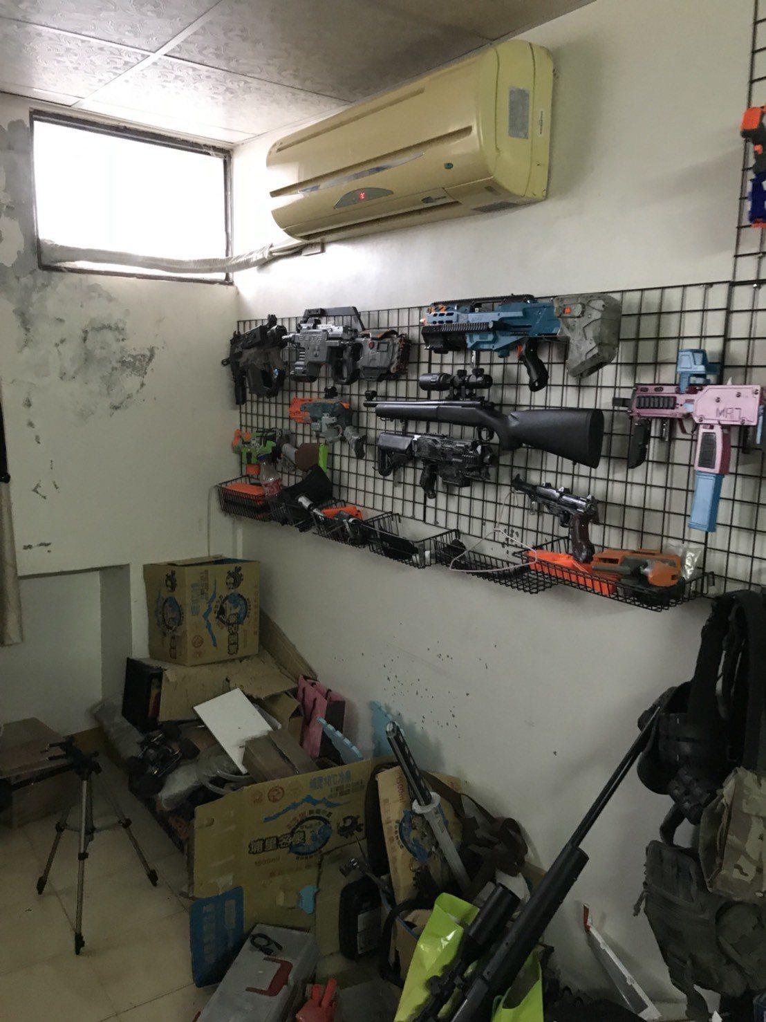 警方在李姓男子(右)家中查獲大批改造槍枝工具、改造槍枝,李將槍枝懸掛在房間牆壁上...