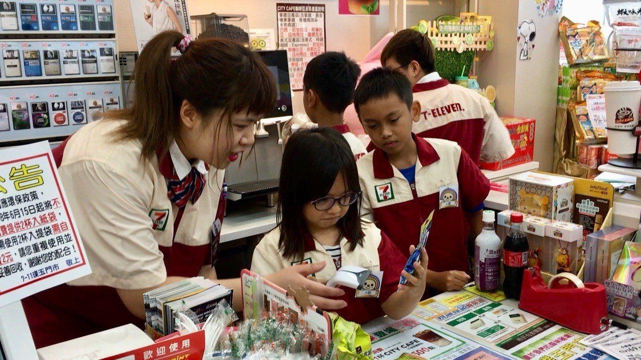 小小店長們在7-11店員的指導下,學習如何幫顧客結帳。記者陳斯穎/攝影