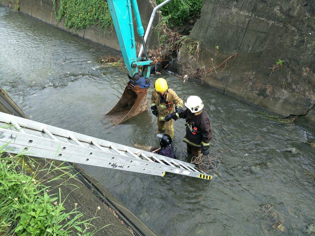殘障婦人騎電動代步車跌落2米深水溝,消防人員和工地怪手一起救援。記者謝恩得/翻攝