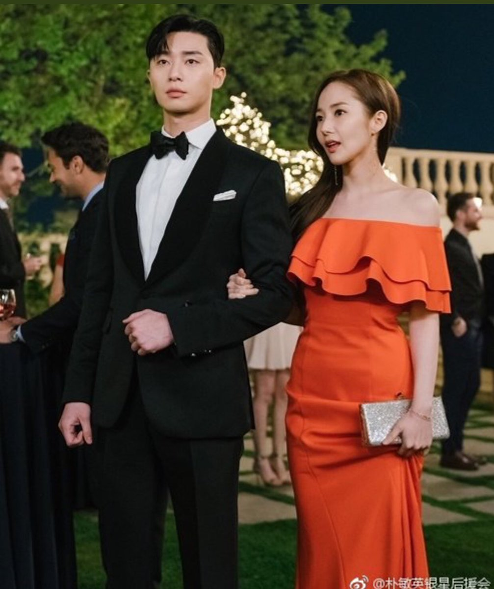 金秘書身穿橘色荷葉邊平肩洋裝搭襯Jimmy Choo金屬手拿包。圖/取自twit...