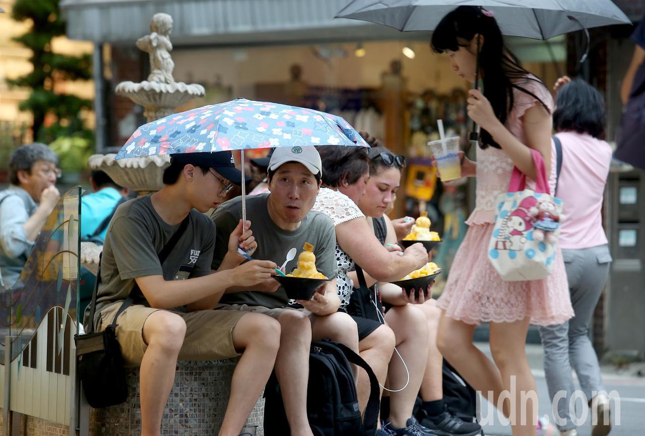 民眾無畏小雨,坐在永康街路邊吃冰。記者余承翰/攝影