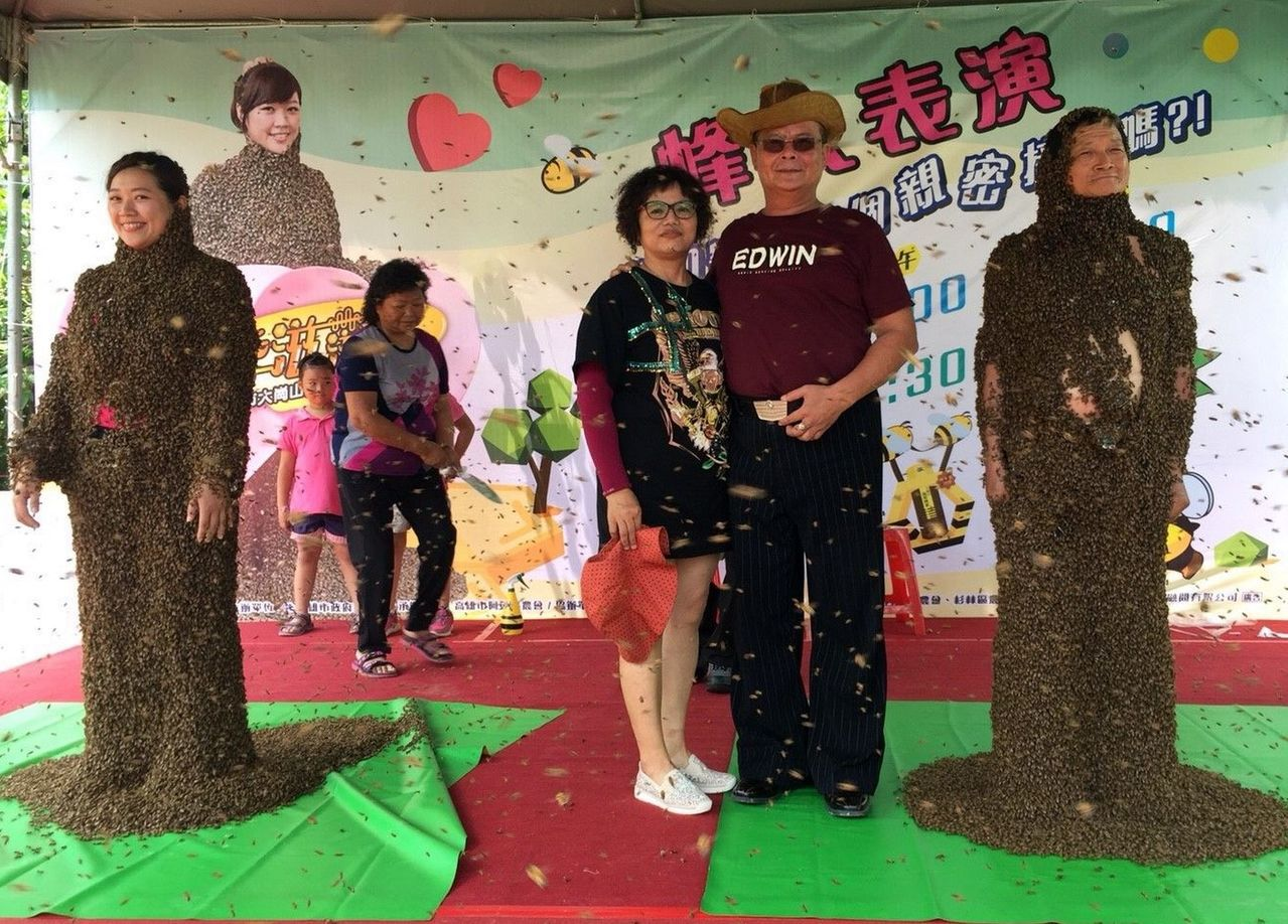 蜂農王信和(右一)偕女兒王玉芬(左一)同台演出「美媚蜂人秀」,民眾爭相合影。記者...