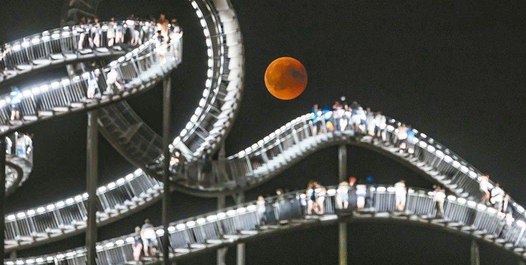 本世紀最長月全食創造許多美景,例如「血月亮」映照著德國知名地標「臥虎藏龜,魔山」...