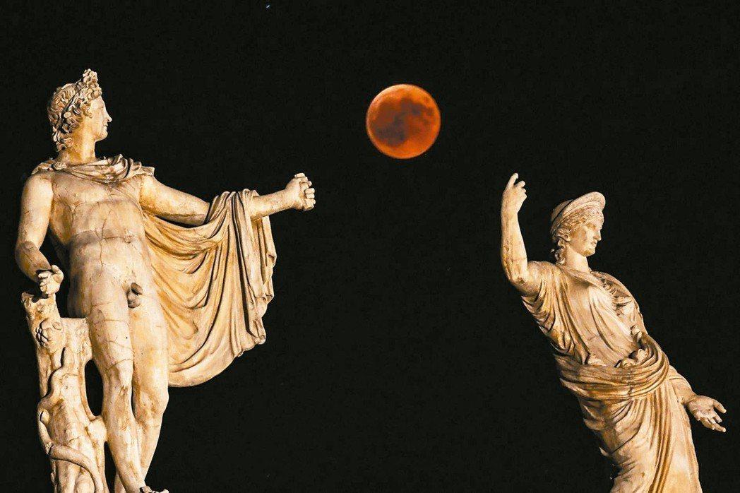 罕見天文奇景「血月亮」,現身在赫拉(左)和阿波羅雕像間的夜空。