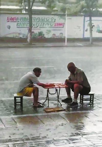 鄭州倆大爺暴雨中下棋成網紅。 圖擷自微博