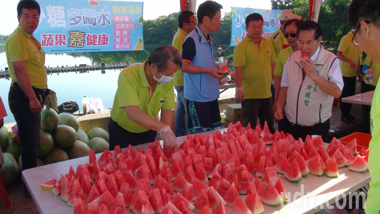 今天在健走活動現場,嘉義果菜市場總經理陳火川擔任志工,贊助大西瓜為參加者消暑,並...