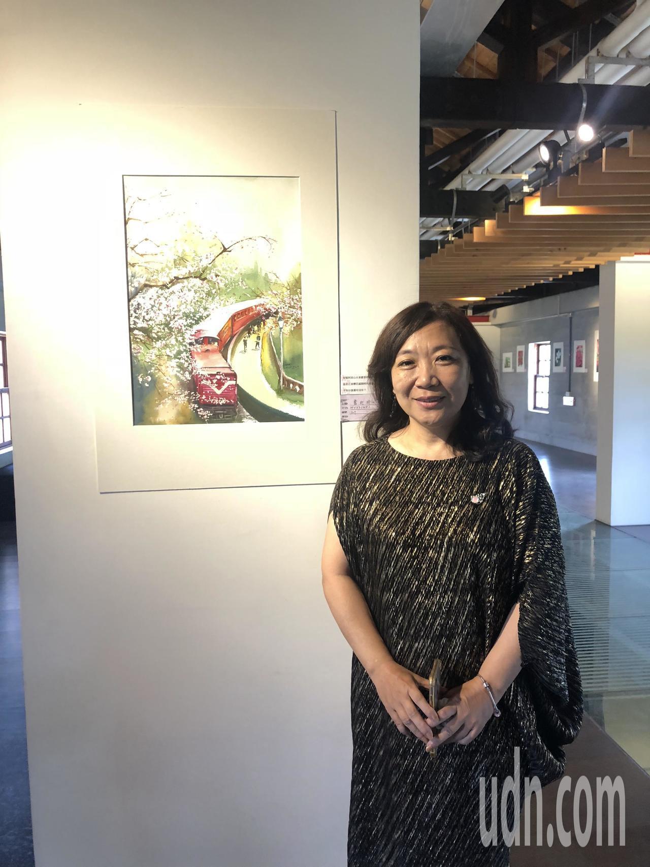 「美當下」諶麗美水彩畫展即日起在嘉義文創園區展出,她身旁的作品是阿里山火車。記者...