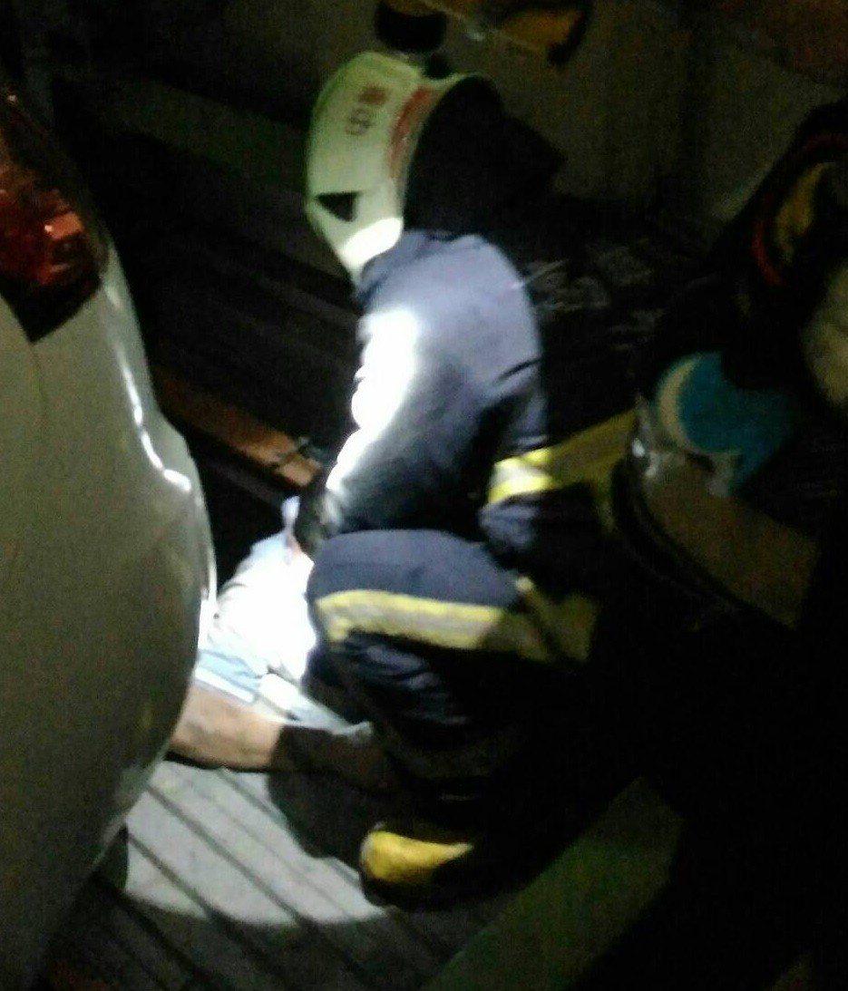 胡姓計程車司機不小心掉落機械停車位下層,經消防人員救起。記者黃宣翰/翻攝
