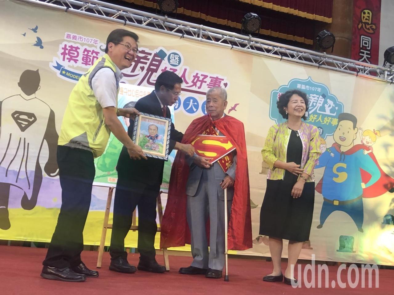 嘉義市長涂醒哲為模範父親得主張清芳繫上超人披風,象徵父親就像超人般守護家庭。記者...
