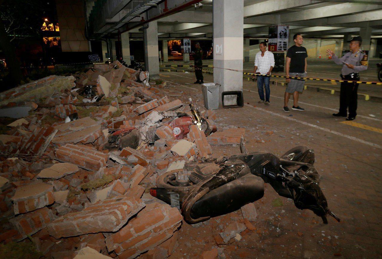 印尼龍目島5日發生強震,把附近峇里島的一間購物中心的磚牆震垮,壓到摩托車。路透