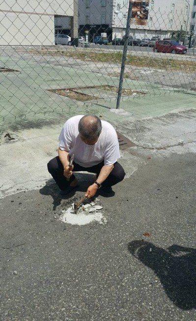 高雄市曾姓老翁為占車位,在馬路上以水泥灌漿埋鐵環,警方找到老翁將鐵環移除。記者黃...
