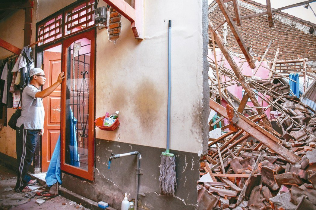 印尼龍目島遭強震襲擊,一名男子看著他幾乎全毀的家。 路透