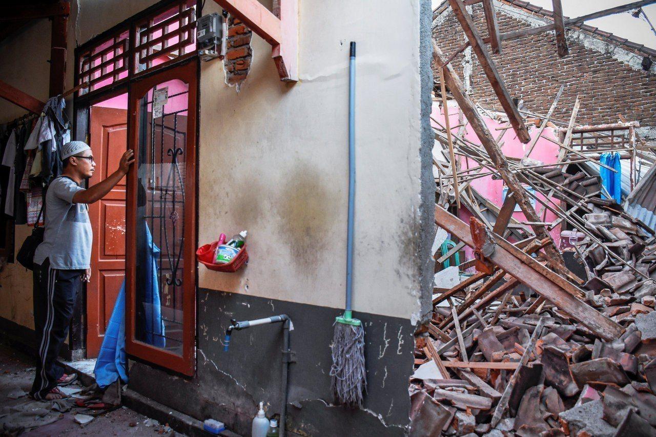 印尼龍目島遭強震襲擊,一名男子看著他幾乎全毀的家。路透