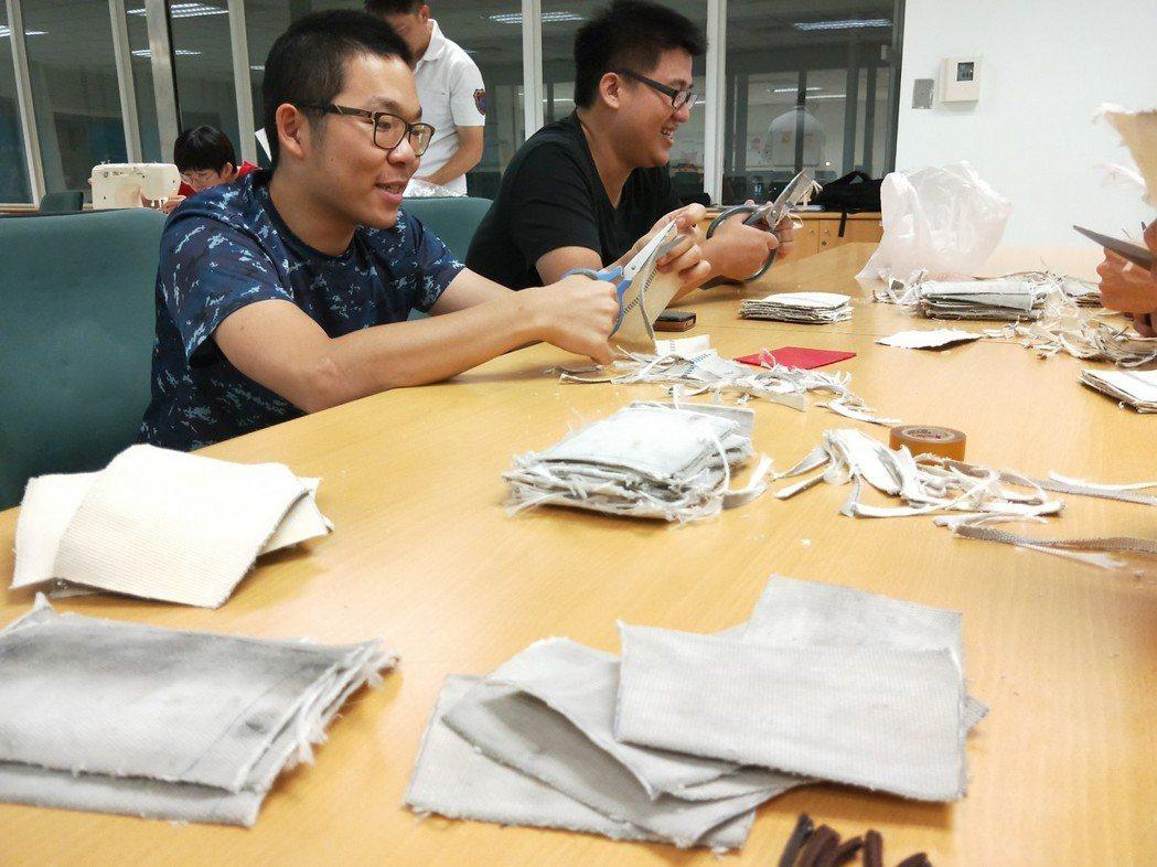 成功分隊替代役男們一起幫忙準備將廢氣消防水帶,製作成環保杯袋。 記者劉星君/翻攝