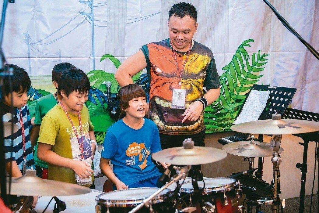 鼓手郁文(右)教導小朋友敲打正確節拍。 新光人壽/提供
