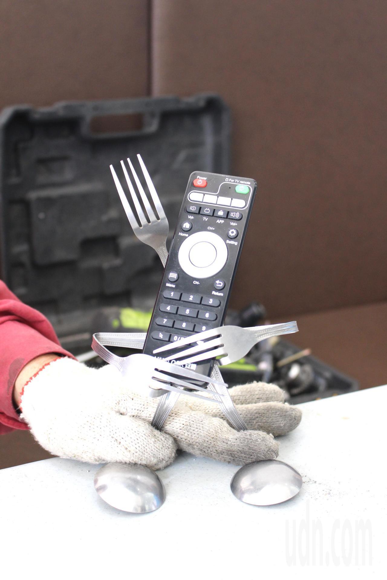謝照基隨手就把生活中的湯匙、叉子等鐵製餐具,創作一個機器人手機架。記者張雅婷/攝...