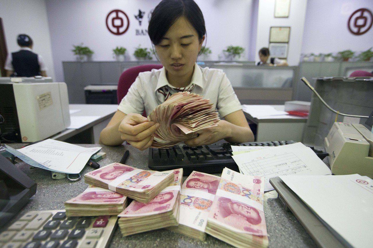 大陸官方將穩定投資增長,加大對目標地區的基礎設施投資。圖為銀行工作人員清點鈔票。...