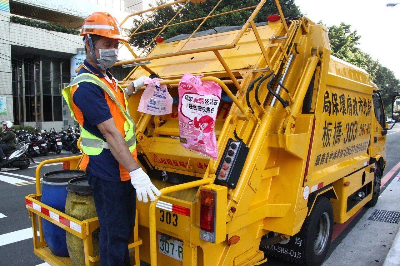 新北環保局清潔隊員收垃圾時會站在車後。圖/本報資料照片