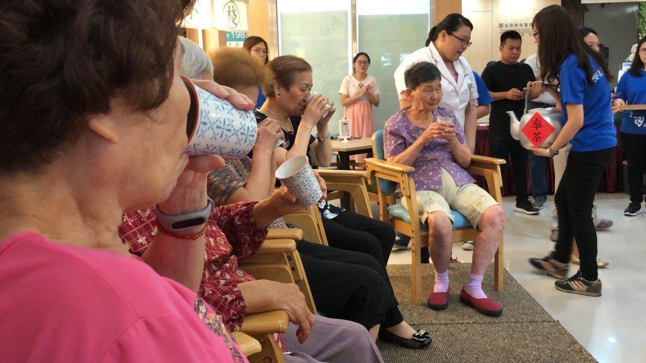 光田日照中心長輩在專員帶領下,演出音樂輔療課程,演出結束後更為長輩奉茶感謝。圖/...