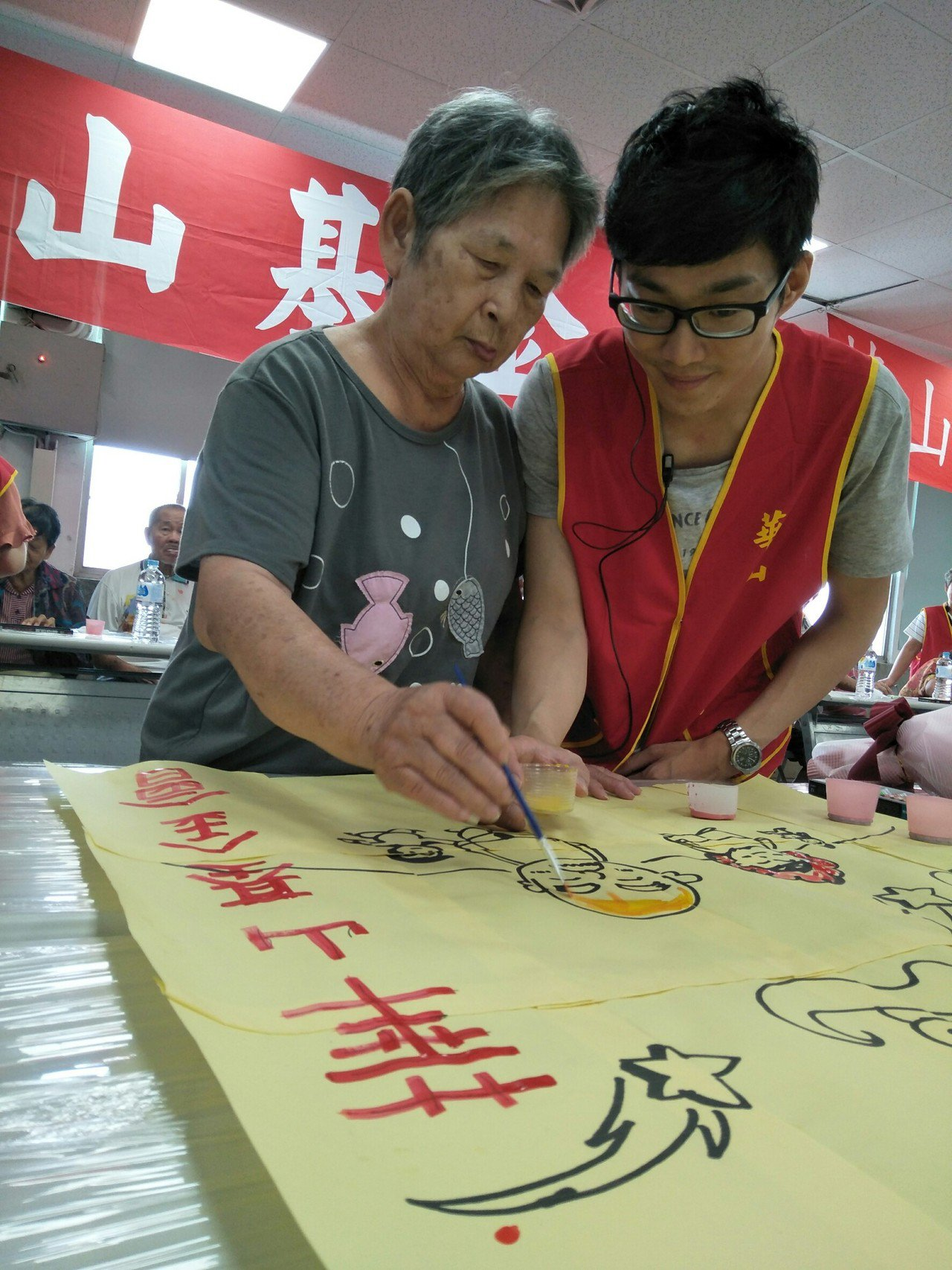 何秀蓮(左)在華山基金會站長黃洋騰(右)協助下,塗滿象徵幸福的圖案。記者徐如宜/...
