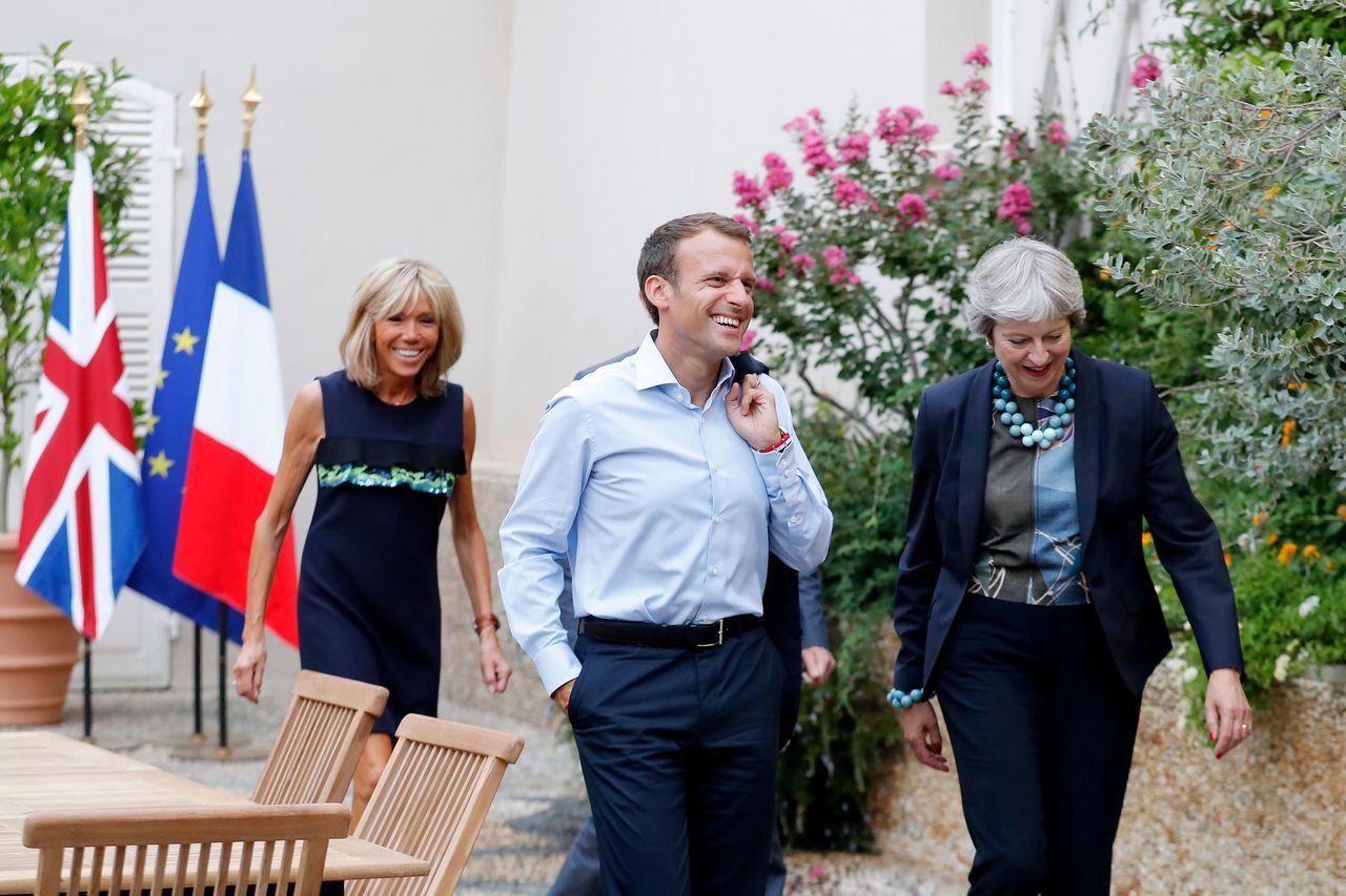 英國首相梅伊(右)3日到南法布赫崗松堡的總統行宮,會晤法國總統馬克宏(中),左為...