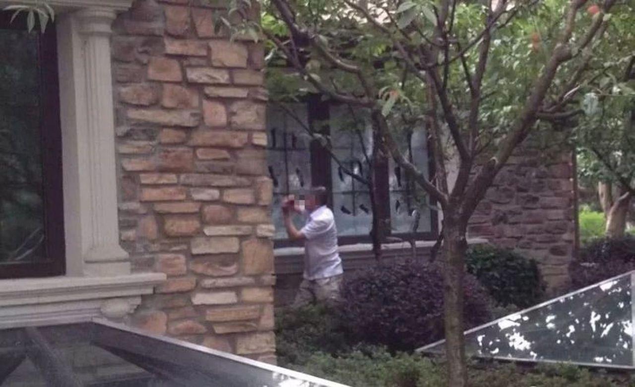 付迪拍到丈夫在砸自家玻璃。(取材自重慶時報)